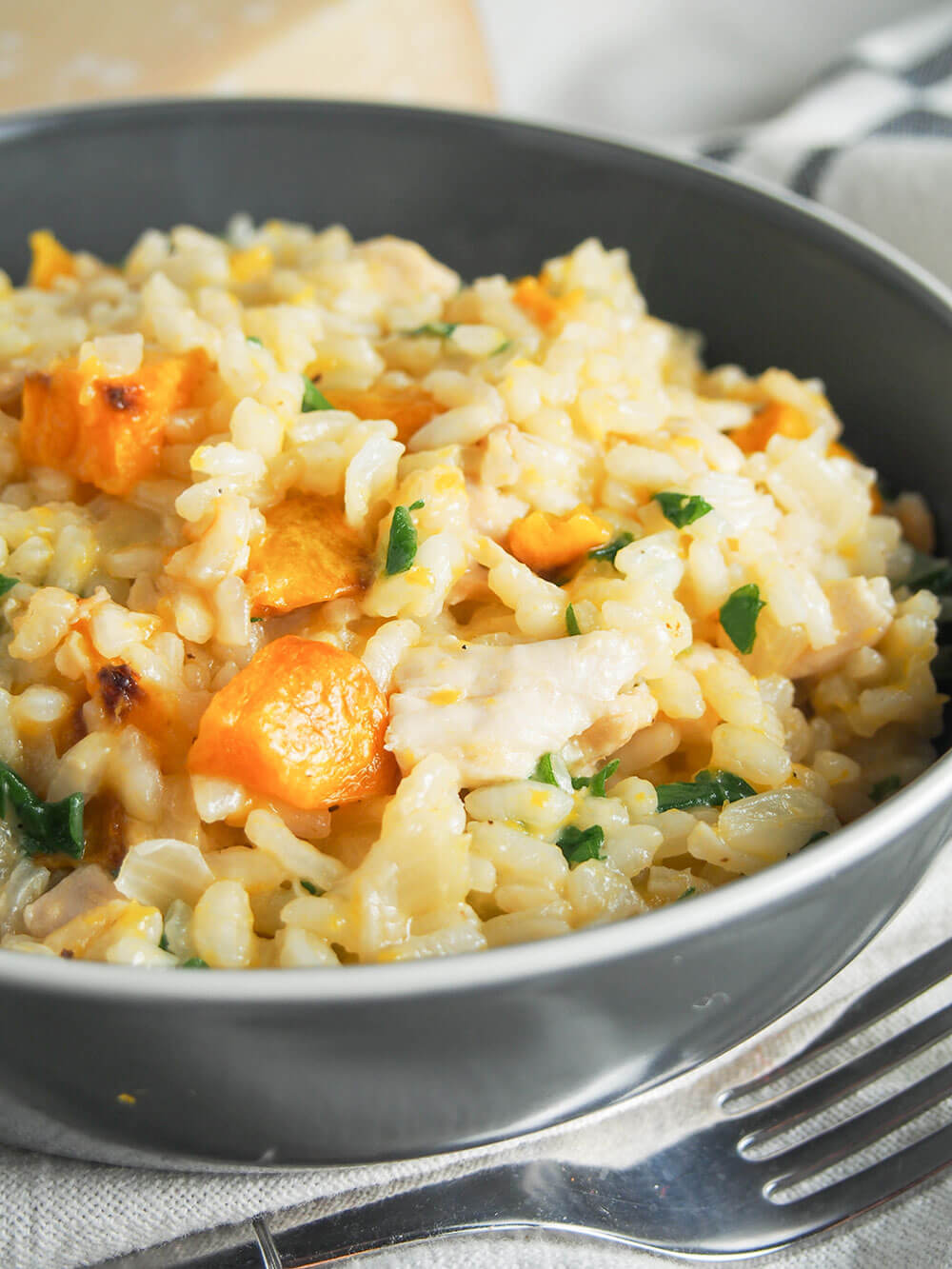 butternut squash risotto with chicken and arugula close up
