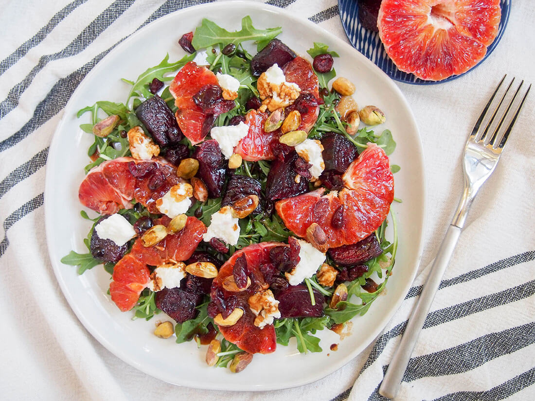 Beet and blood orange salad on plate with fork to side