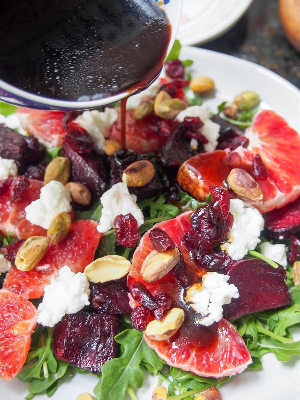 adding dressing to beet and blood orange salad