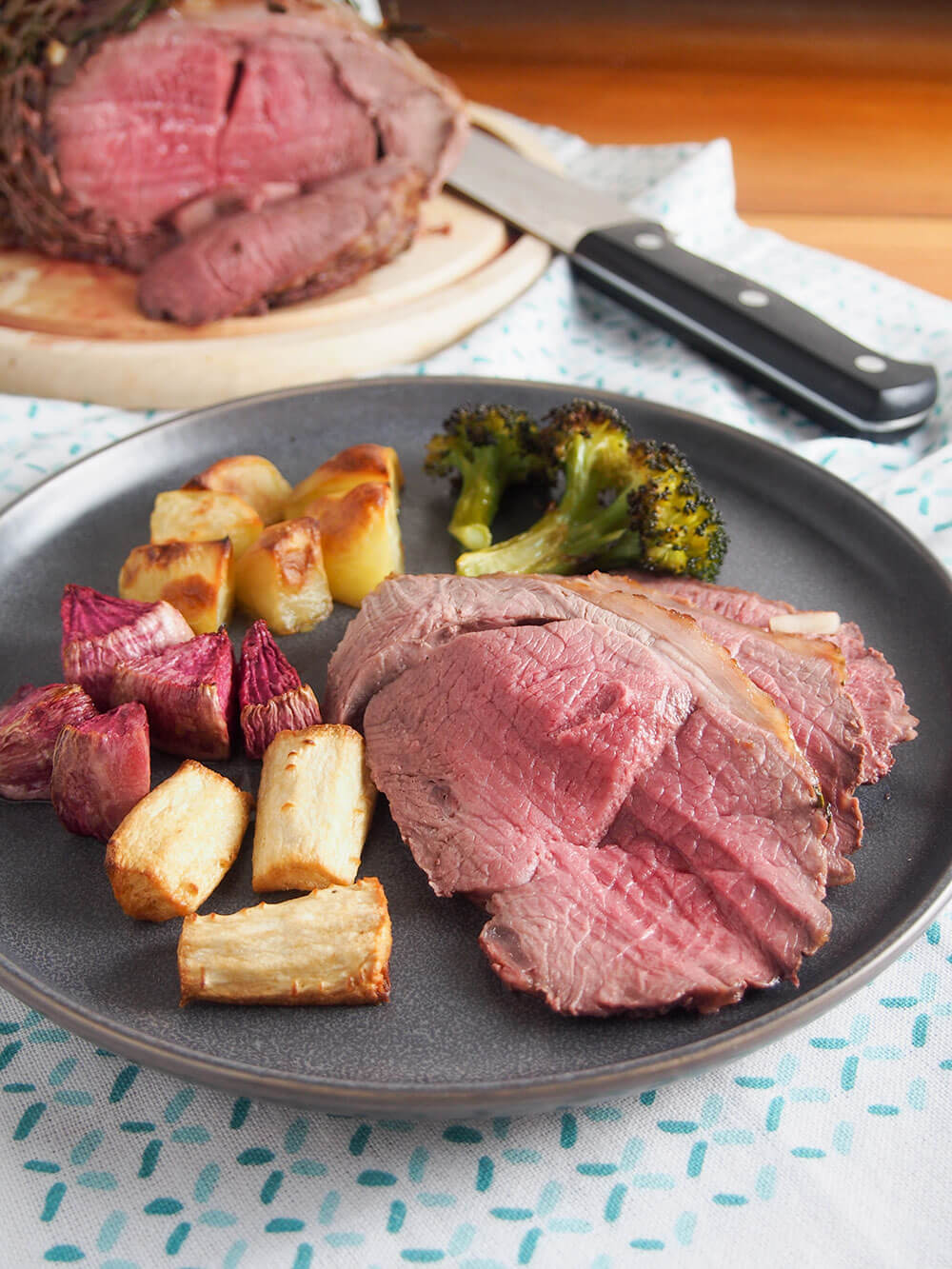 Roast lamb on plate with vegetables on the side