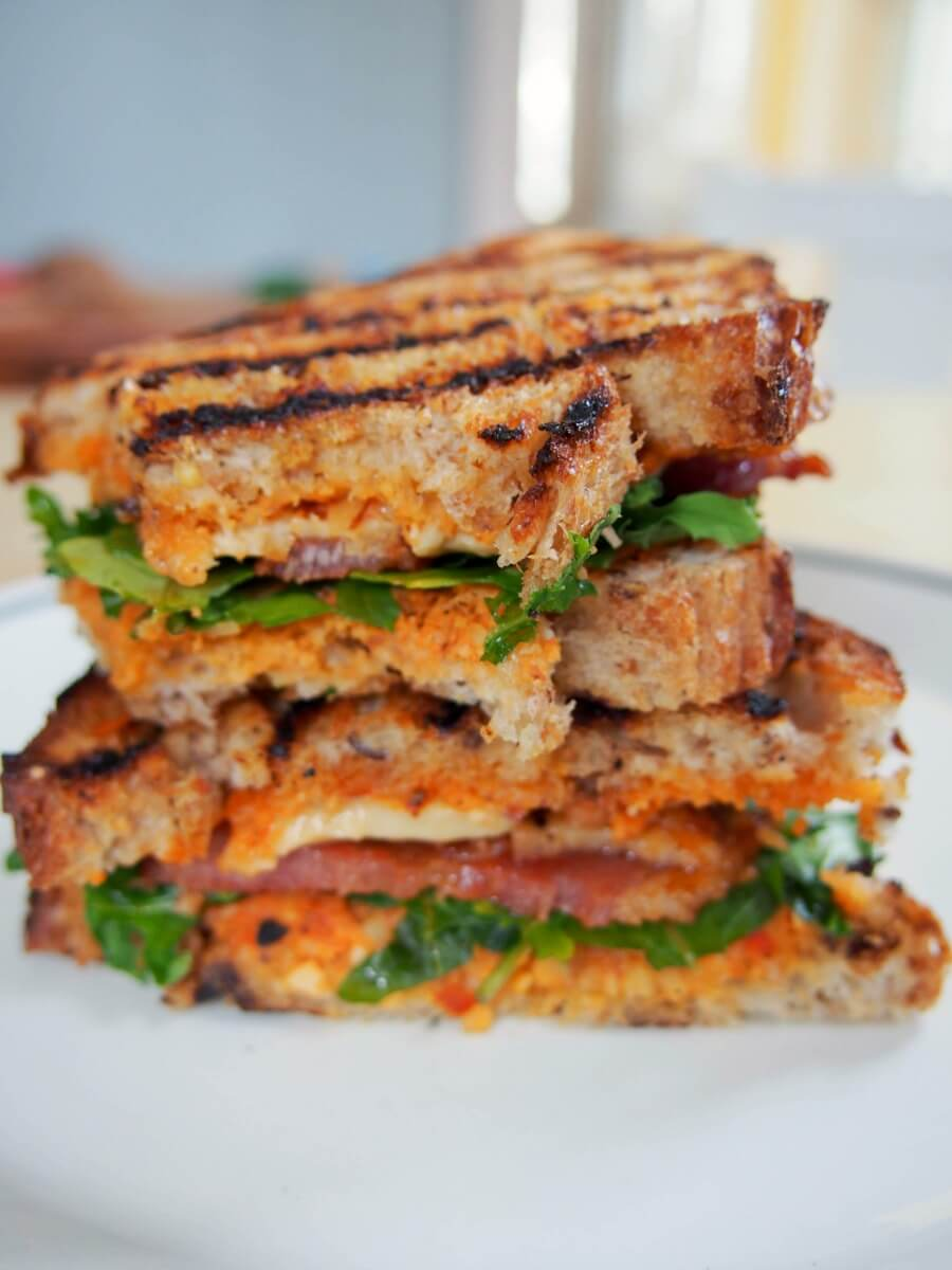 romesco and bacon grilled cheese - This delicious twist on a bacon grilled cheese sandwich piquant romesco sauce along with bacon, smoked cheddar and arugula to create a fantastic lunch.