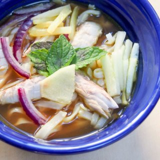 Asam laksa is a deliciously flavorful Asian broth with a fish, tamarind and spicy base, served over rice noodles with cucumber, pineapple and mint garnish.