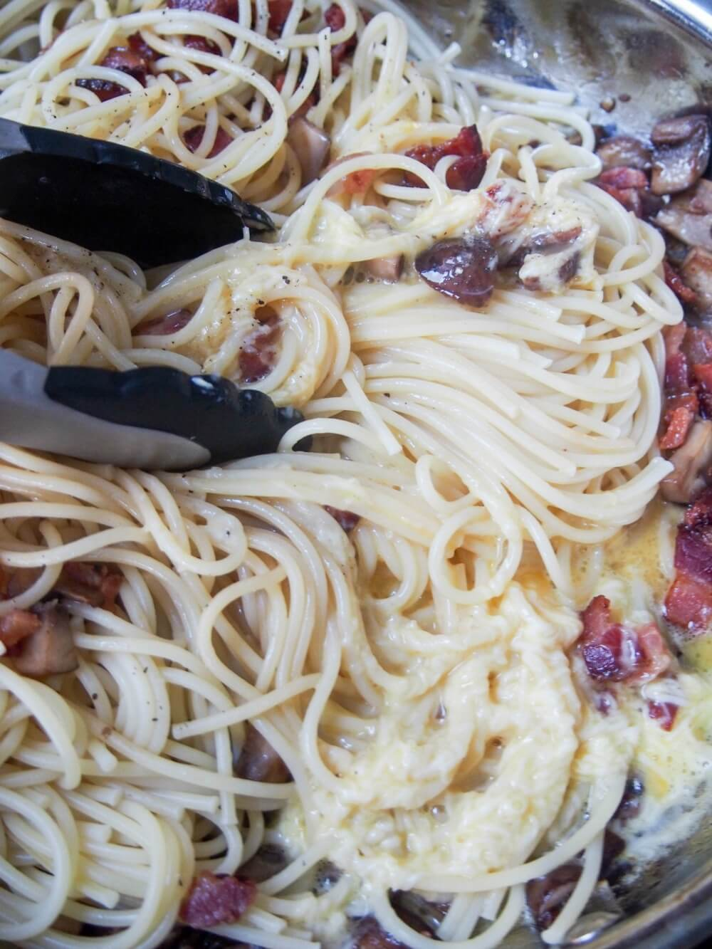making Spaghetti alla carbonara with mushrooms - adding egg-cheese mixture