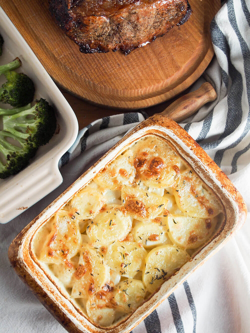 Dauphinoise potatoes served alongside roast beef and broccoli