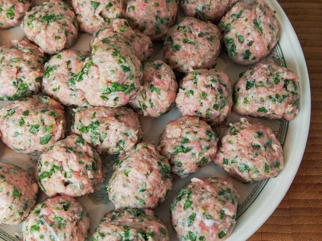 Pork meatballs with arugula and lemon before cooking