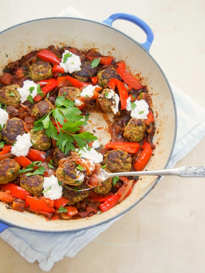 These kofte-style lamb meatballs are delicious with herbs, spices and pine nuts in them, made even better served in a tomato-pepper sauce with a feta-yogurt topping.