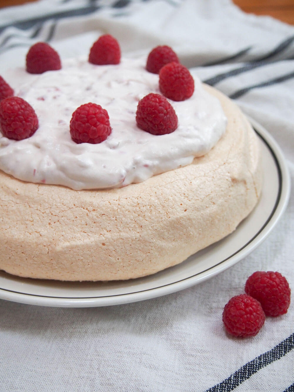 pavlova with raspberries and cream on plate