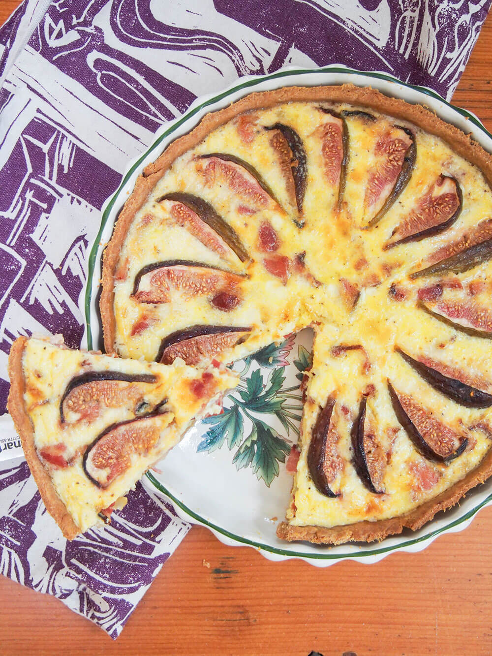 fig, goat's cheese and bacon quiche from overhead with slice cut out