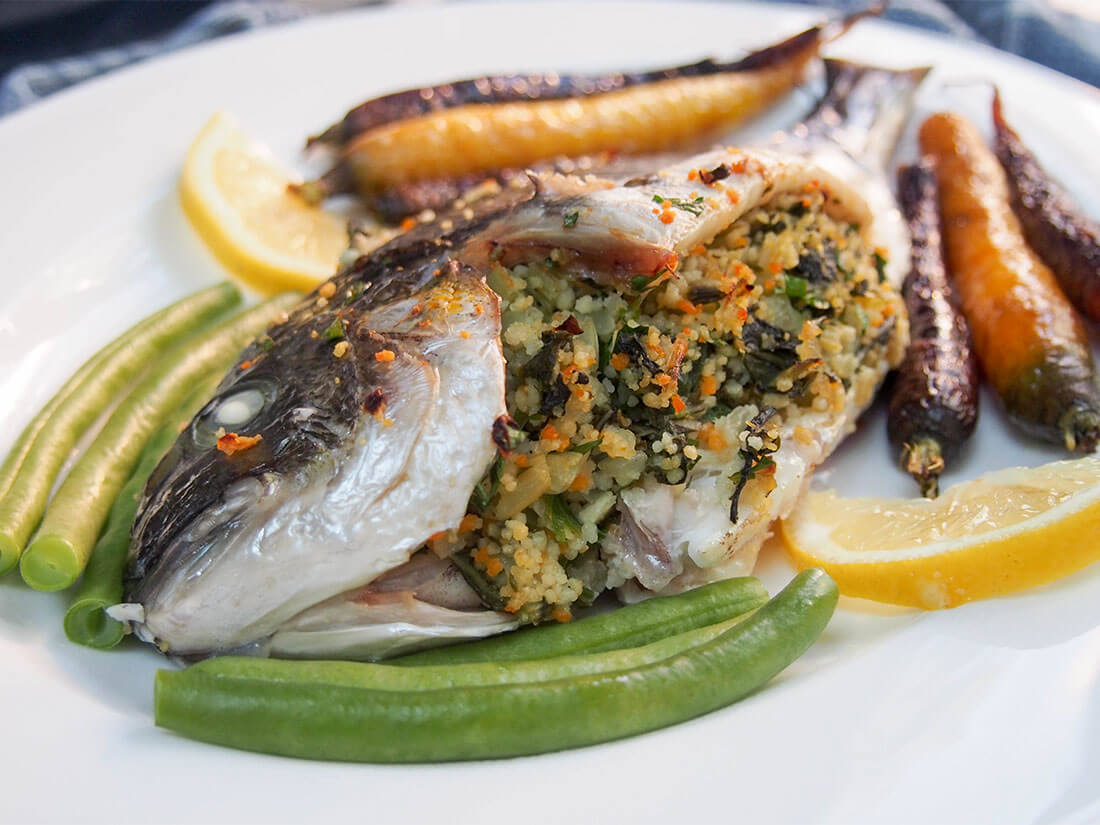 chard couscous stuffed fish on side with vegetables around