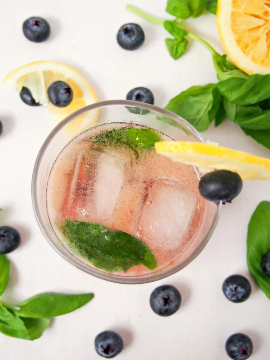This bashful blueberry cocktail is a delicious mix of blueberries, lemon, vermouth, whiskey and a hint of basil. Topped with soda, it's a refreshing drink. Easy to make & enjoy!