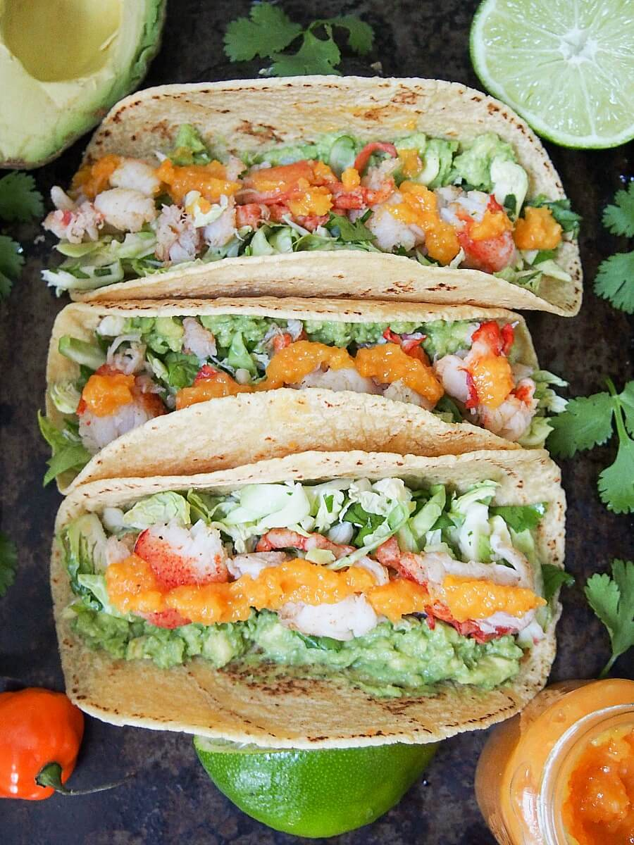 Lobster tacos make such a delicious quick meal. They are light but filling, and a great way to make the slight indulgence of lobster go further. Here served with a simple Brussels sprout slaw, guacamole and mango habanero sauce.