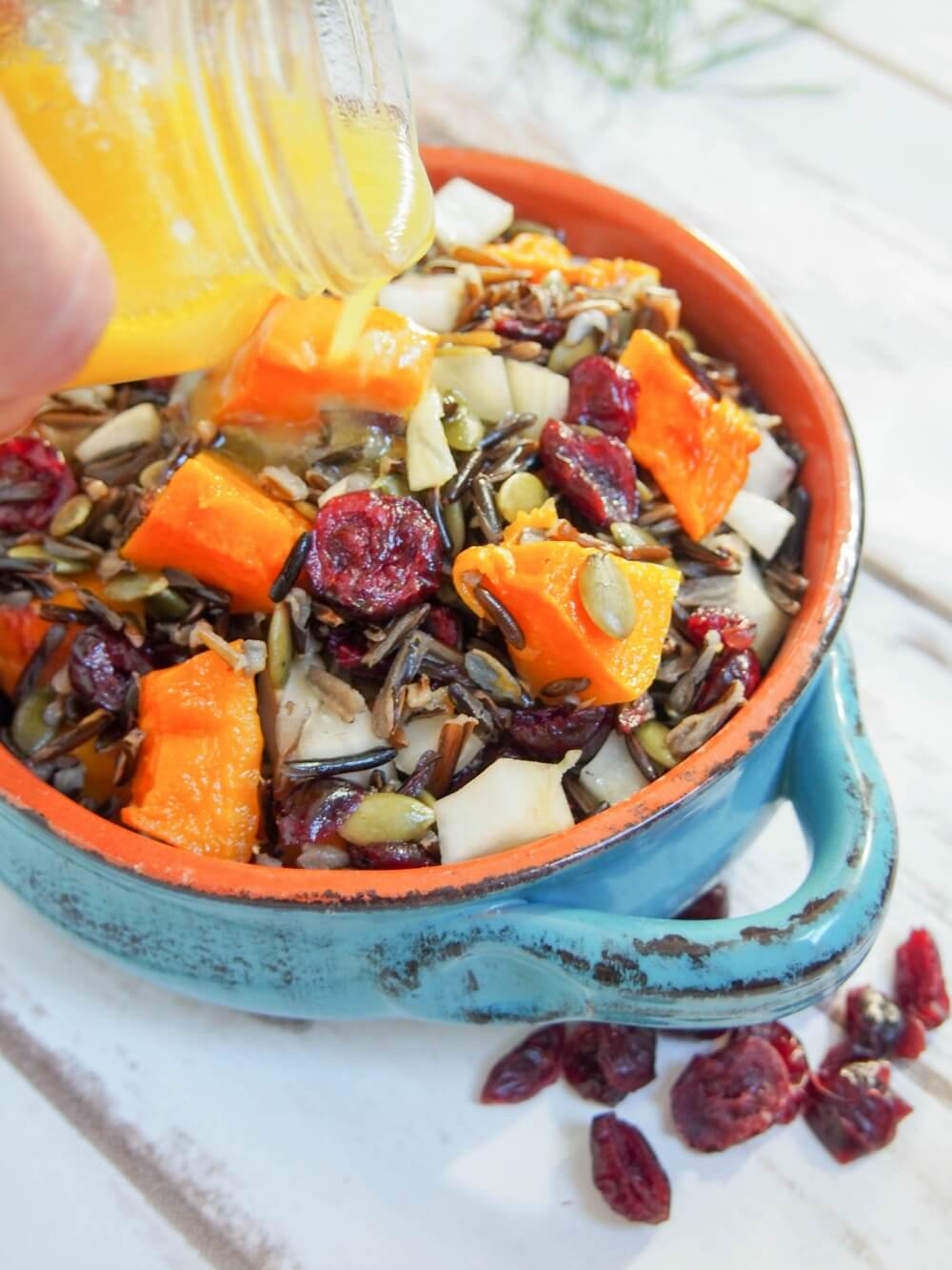 Butternut squash wild rice salad with cranberries and fennel, pouring on the dressing