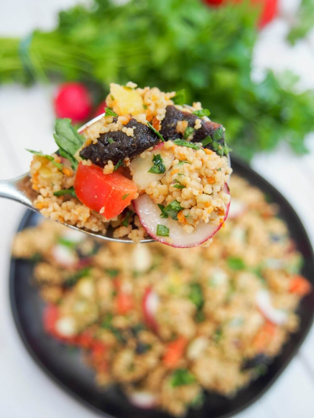 spoonful of couscous salad with prune vinaigrette