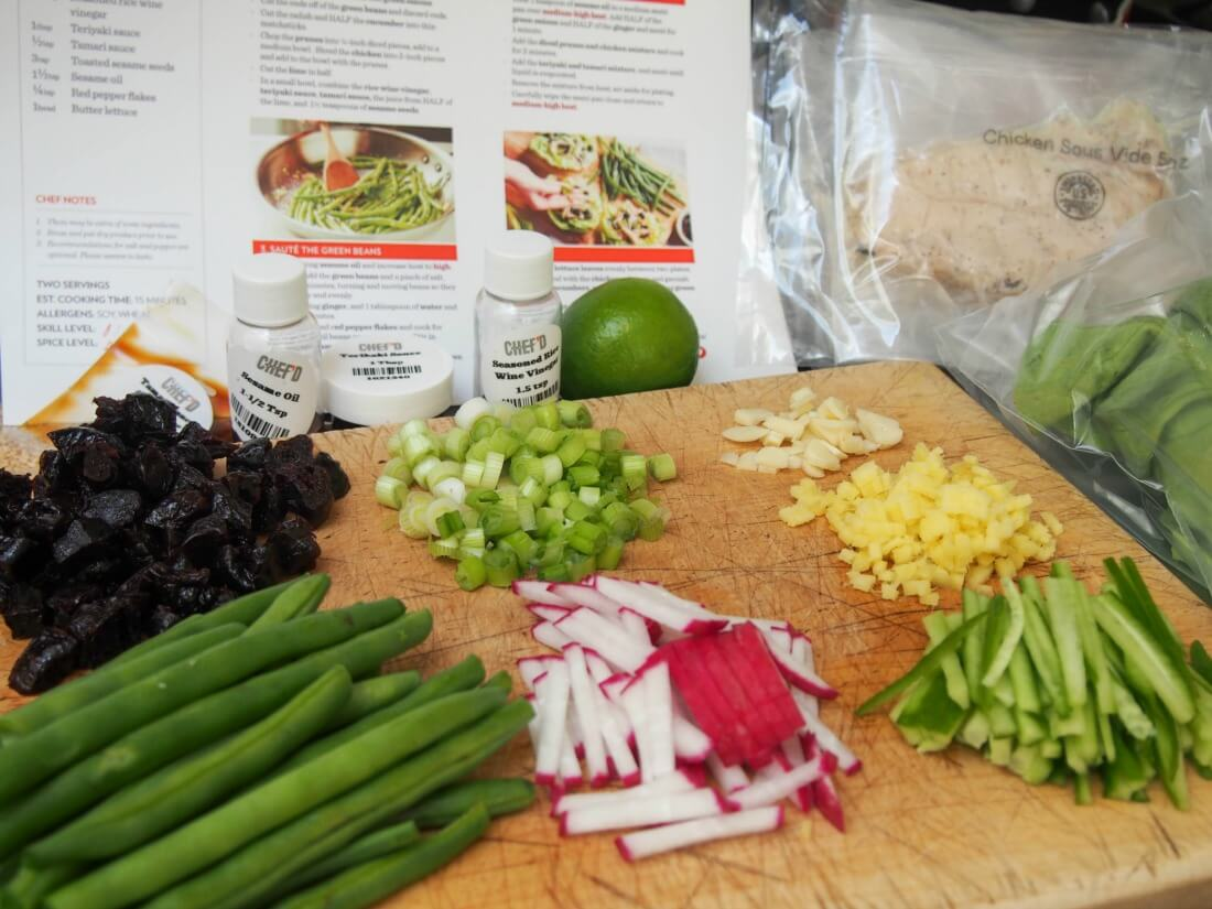 preparing ingredients for Chef'd meal kit: Asian chicken and California prunes lettuce wraps