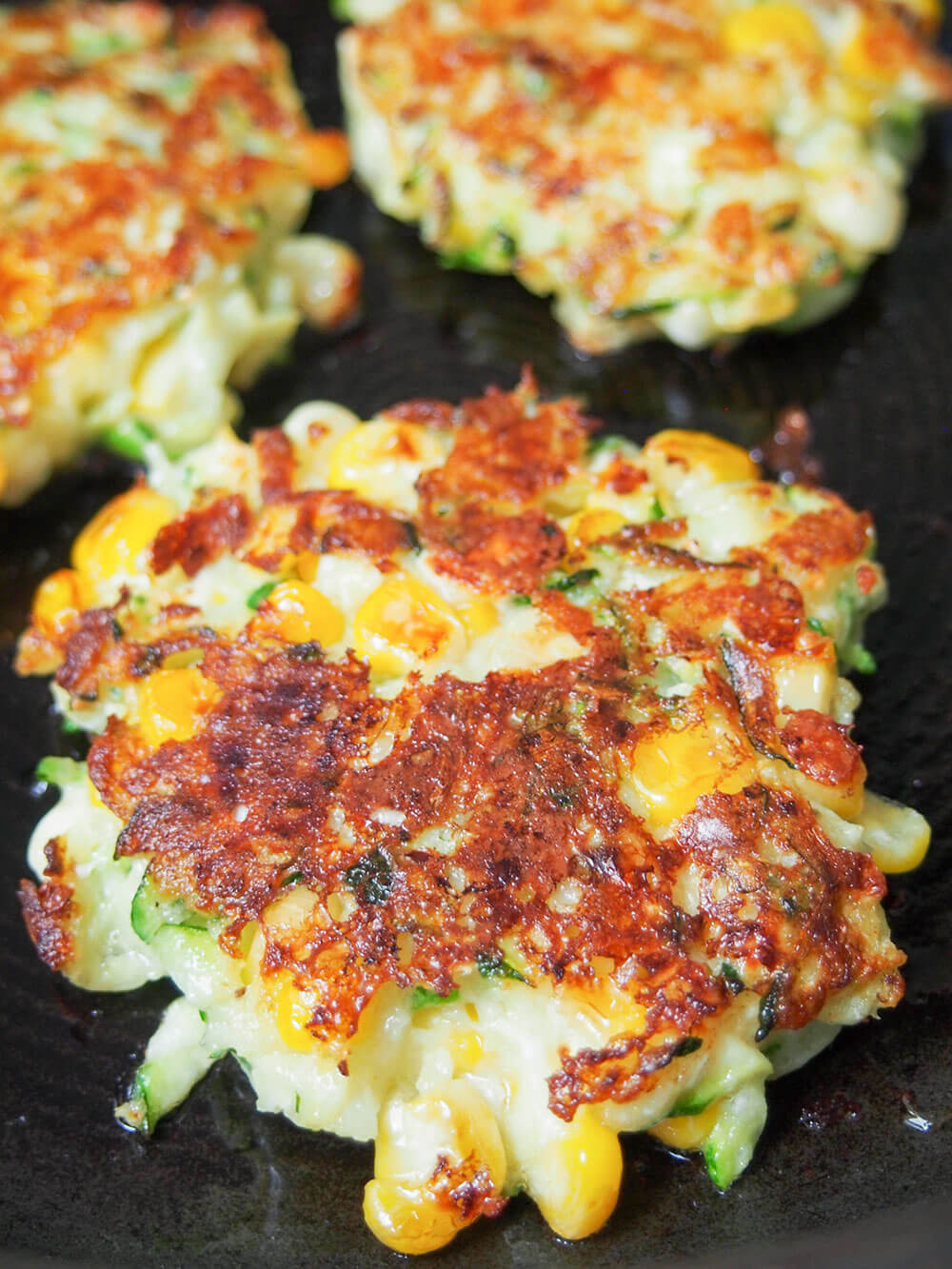 cooking zucchini corn fritters in skillet