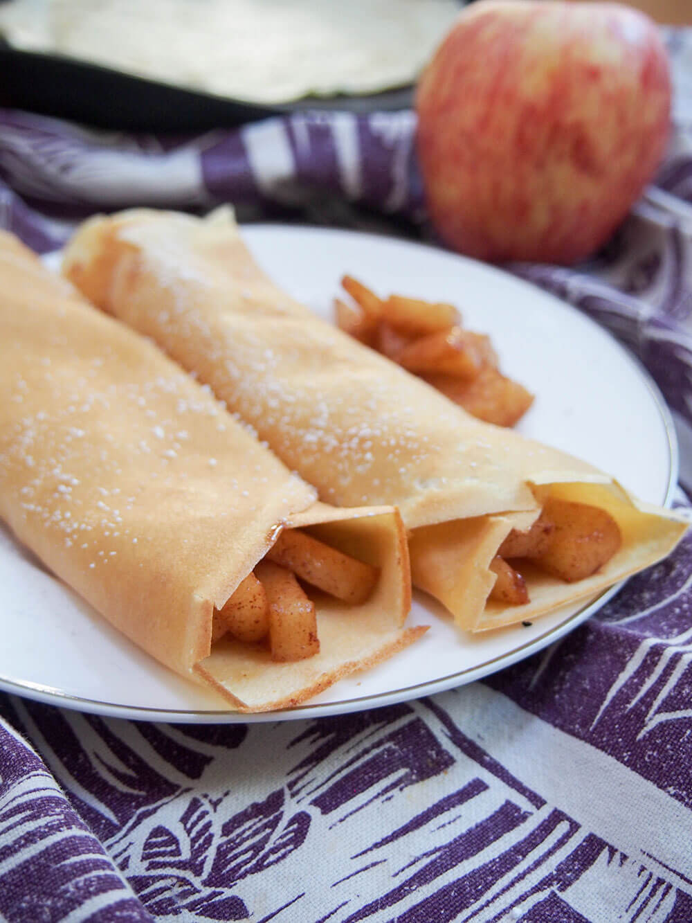 apple crepes from side with apple and extra crepe in background