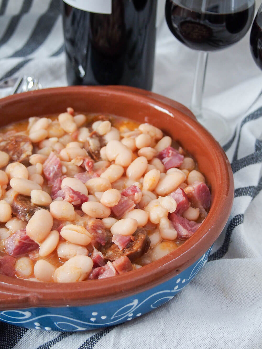 Fabada Asturiana - Asturian white bean stew with wine behind to serve