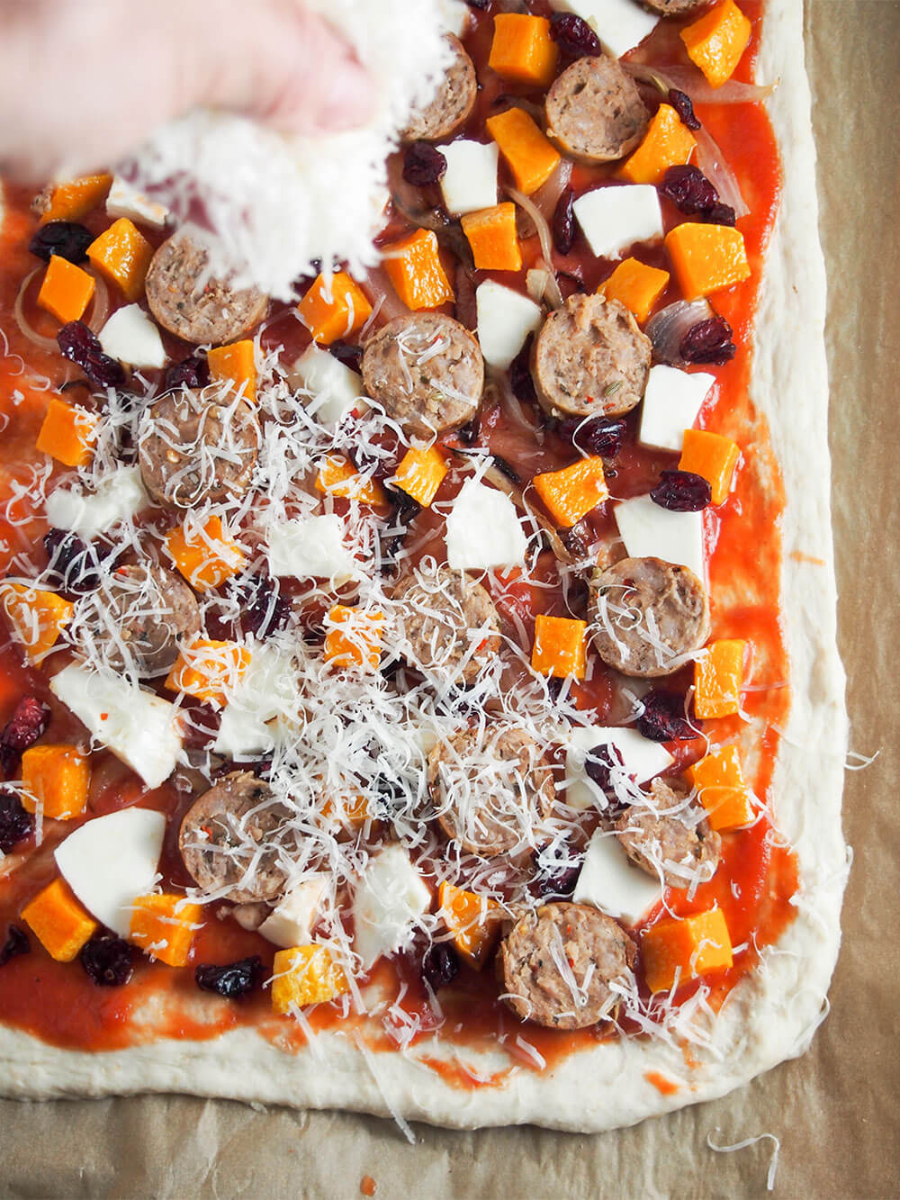 adding cheese to fall pizza with sausage and squash
