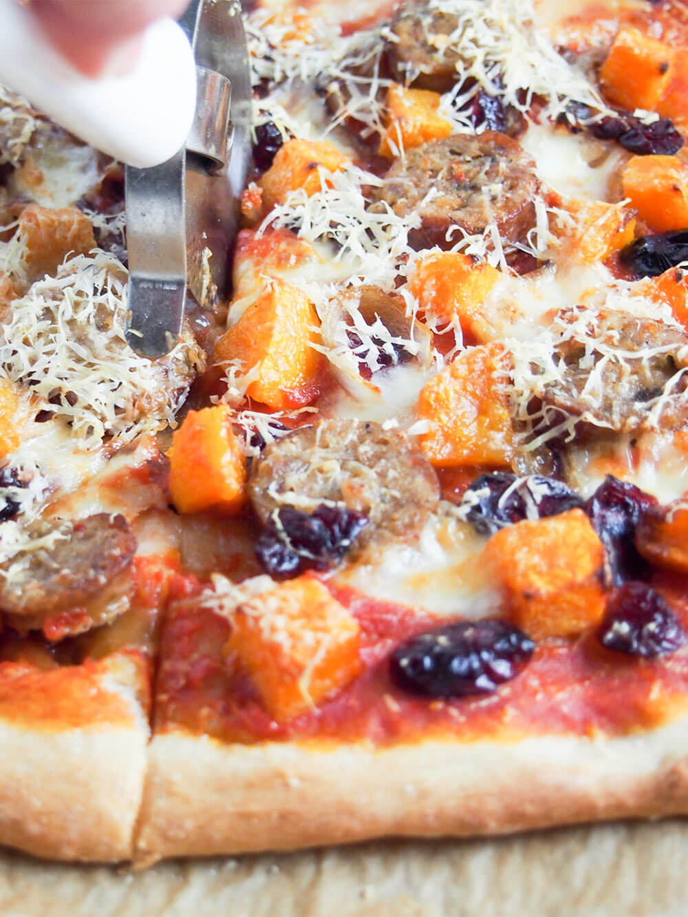 cutting fall pizza with sausage and squash
