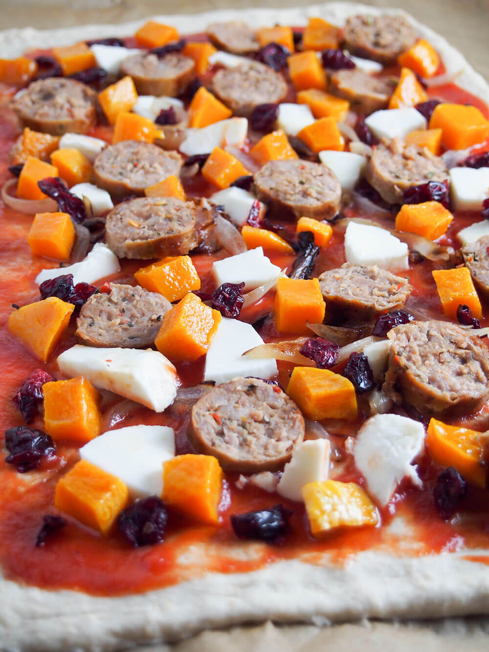 adding toppings to fall pizza with sausage and squash