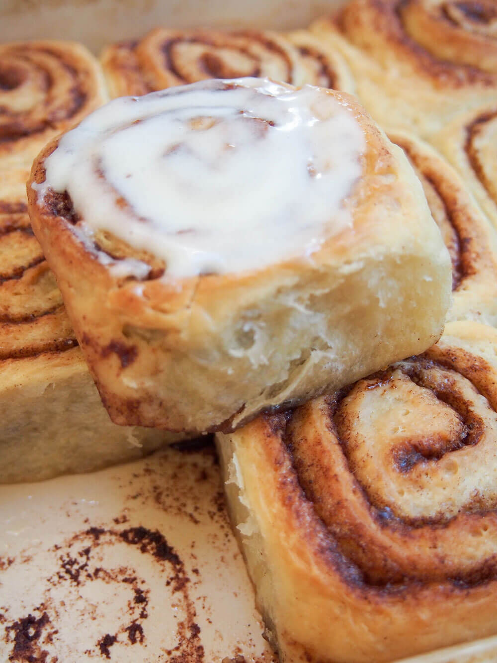 eggnog cinnamon rolls with one topped with frosting on top of others