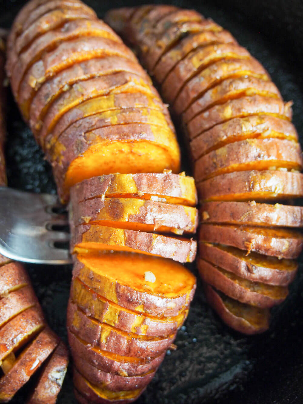 hasselback sweet potatoes - lifting one up with fork
