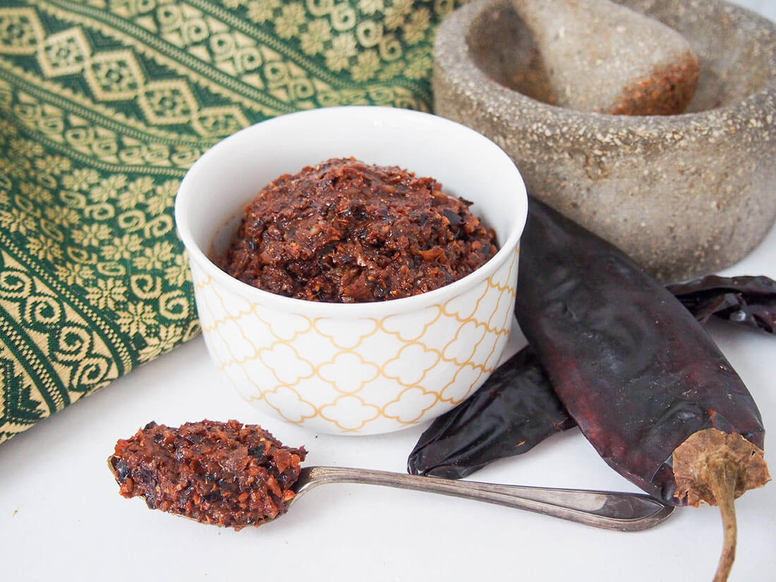 massaman curry paste with chilis and pestle and mortar to side