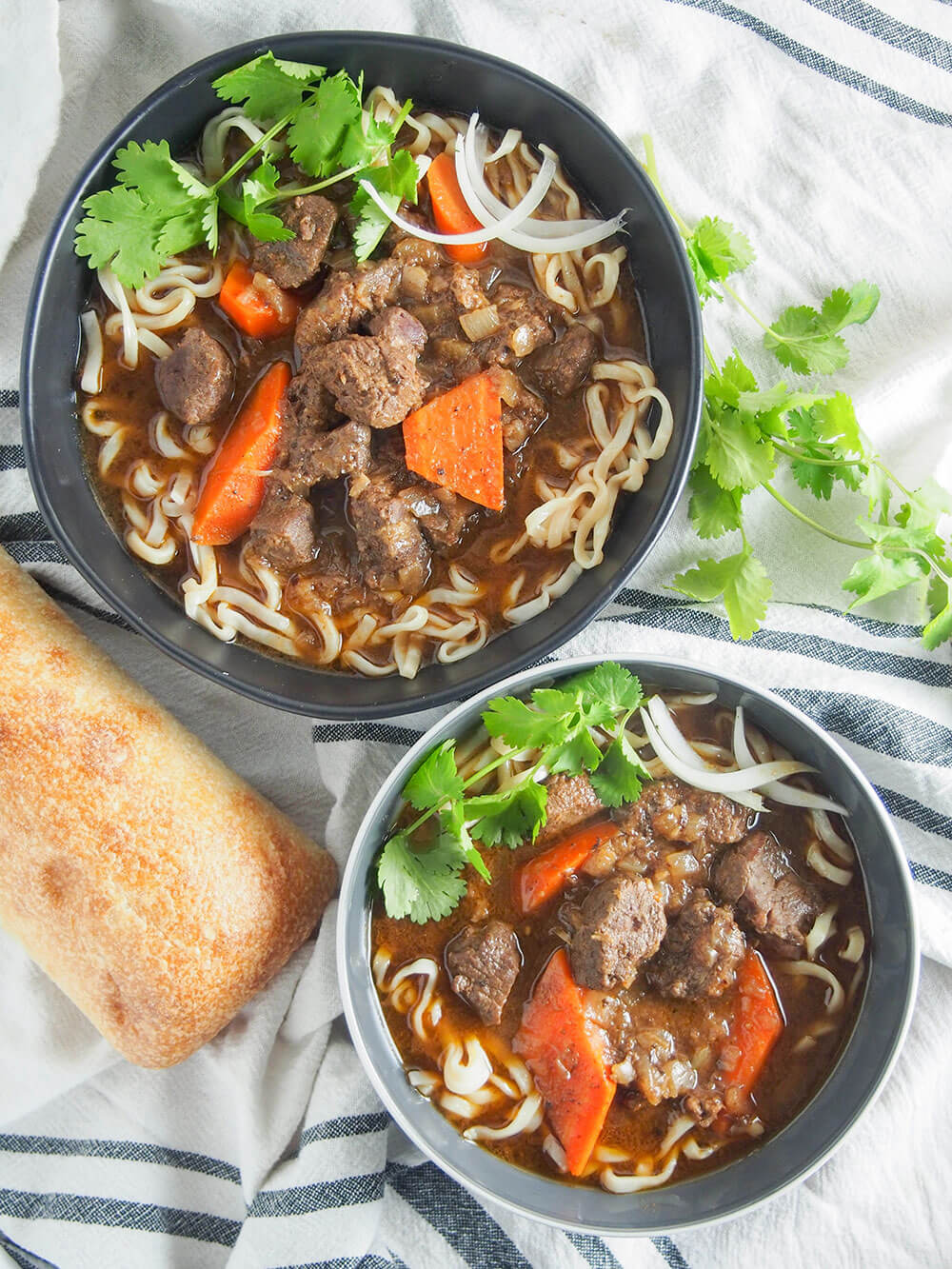 bo kho Vietnamese beef stew over noodles with bread on the side