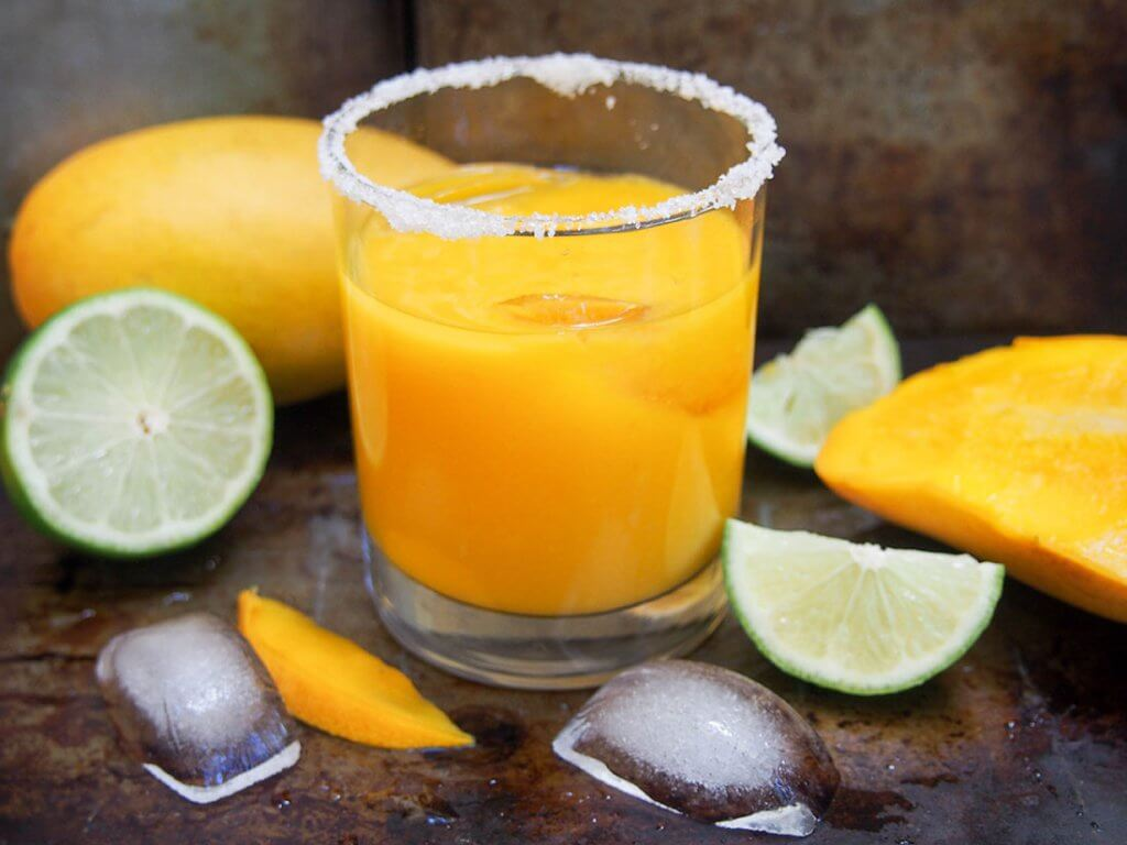 mango margarita with mango and lime to side