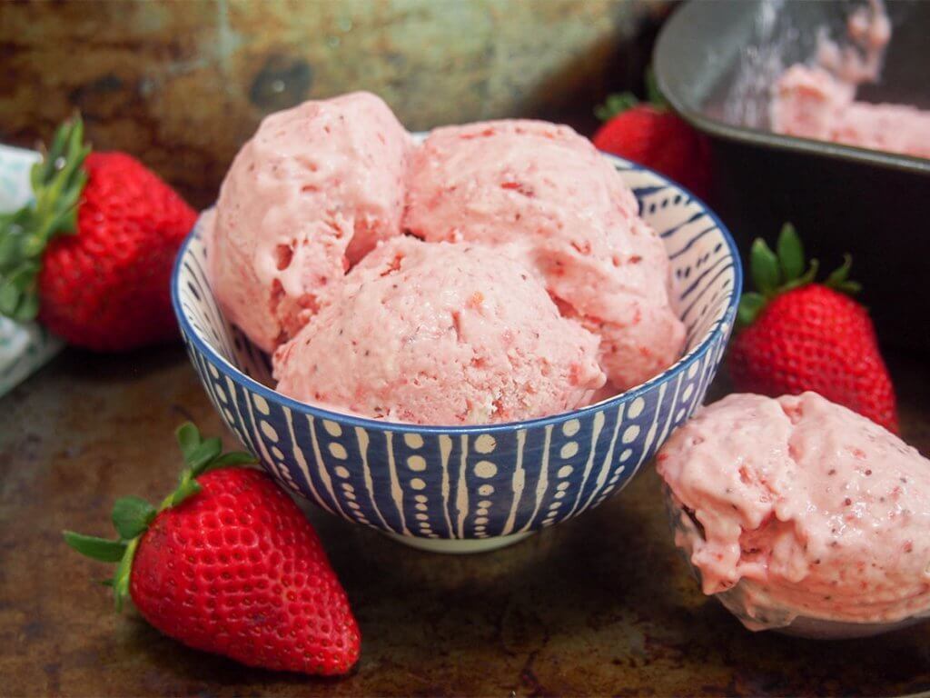 No churn roasted strawberry ice cream in bowl with scoop to side