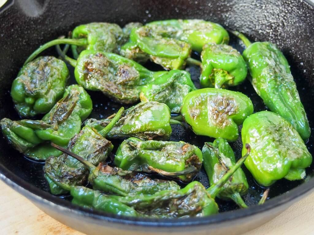blistered Padron peppers close up in skillet