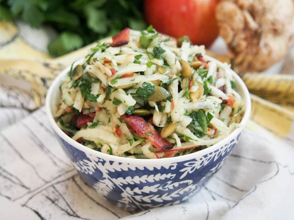 Apple celeriac salad in small bowl in front of some of ingredients