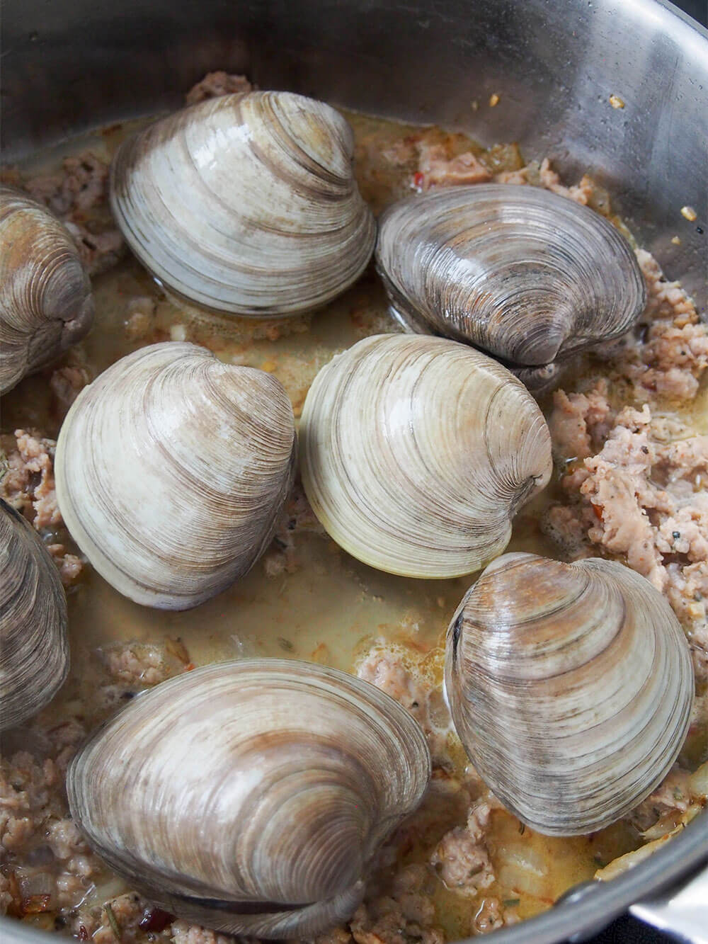 adding clams making pasta with clams and sausage