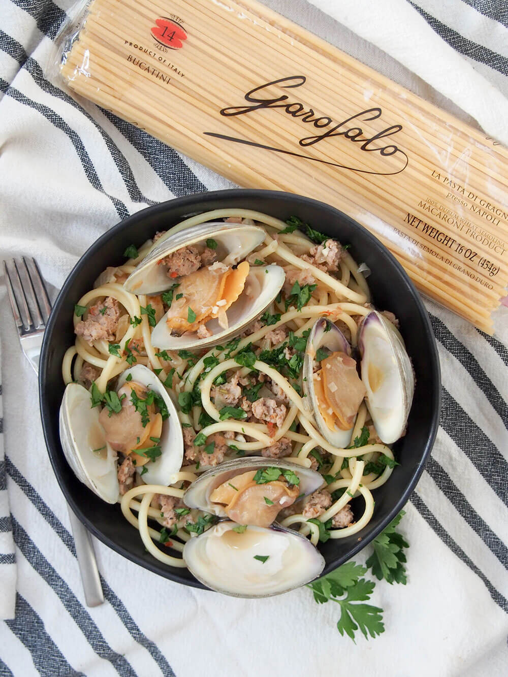Pasta with clams and sausage with pack of pasta to side