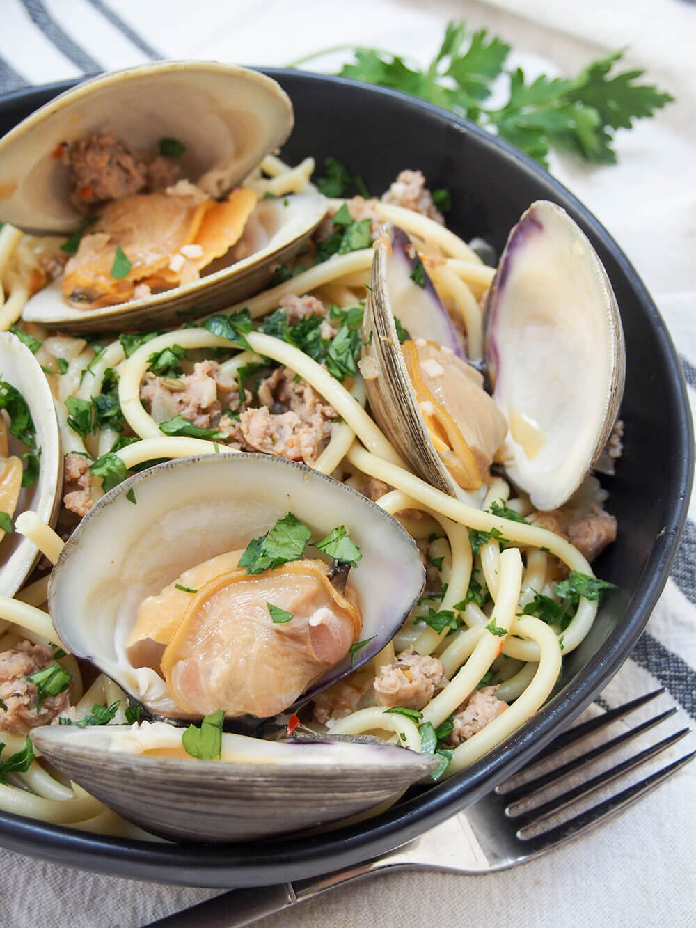 Pasta with clams and sausage in bowl with fork in front