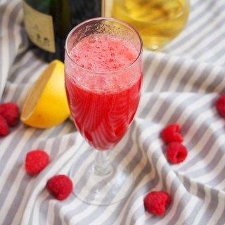 lemon raspberry bellini glass with bottles behind