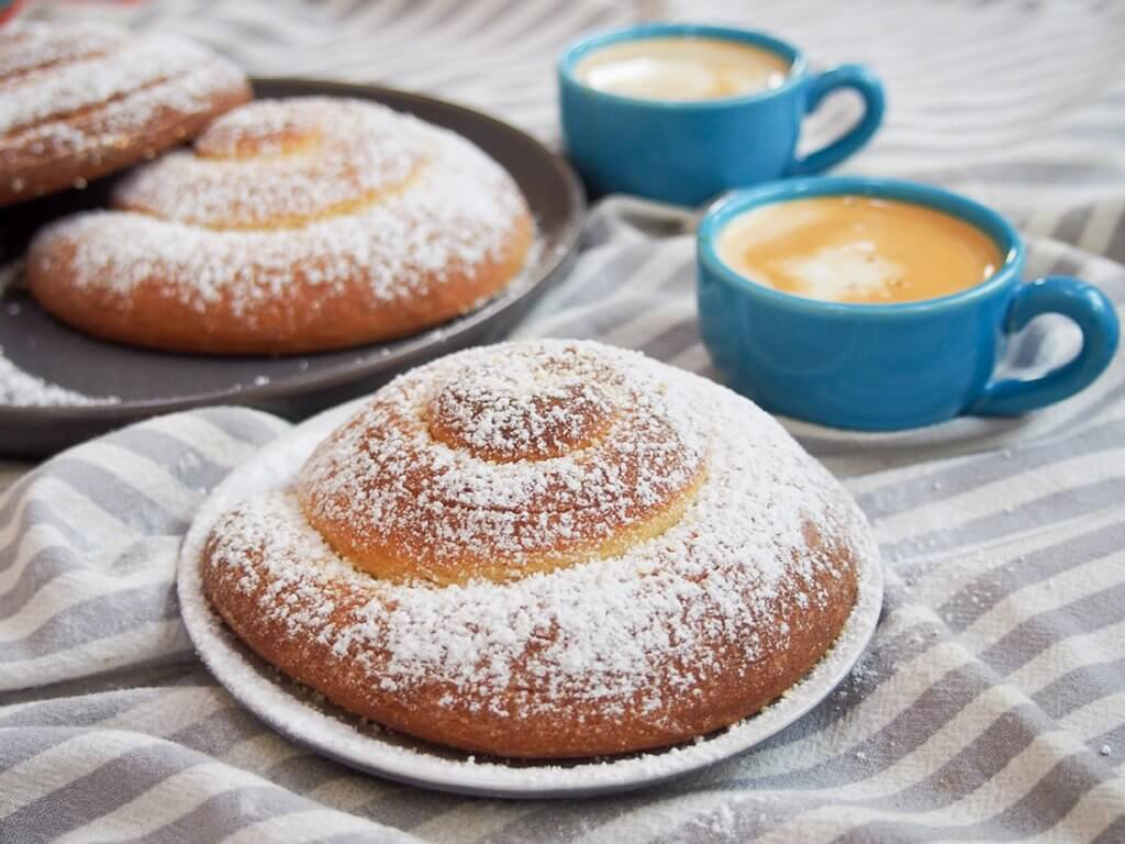Pan de Mallorca (Puerto Rican sweet rolls) - one on plate with more behind