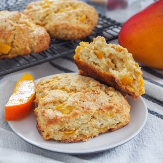 Coconut mango scones with one whole and one split on plate