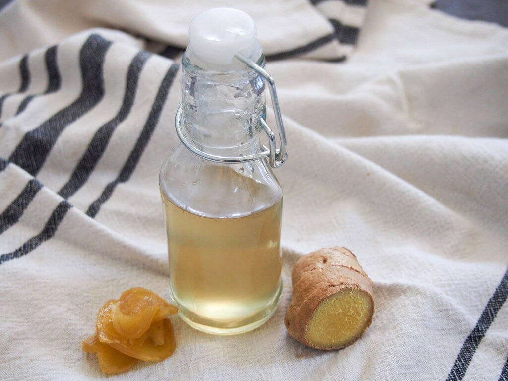 bottle of ginger syrup with piece of fresh ginger to side