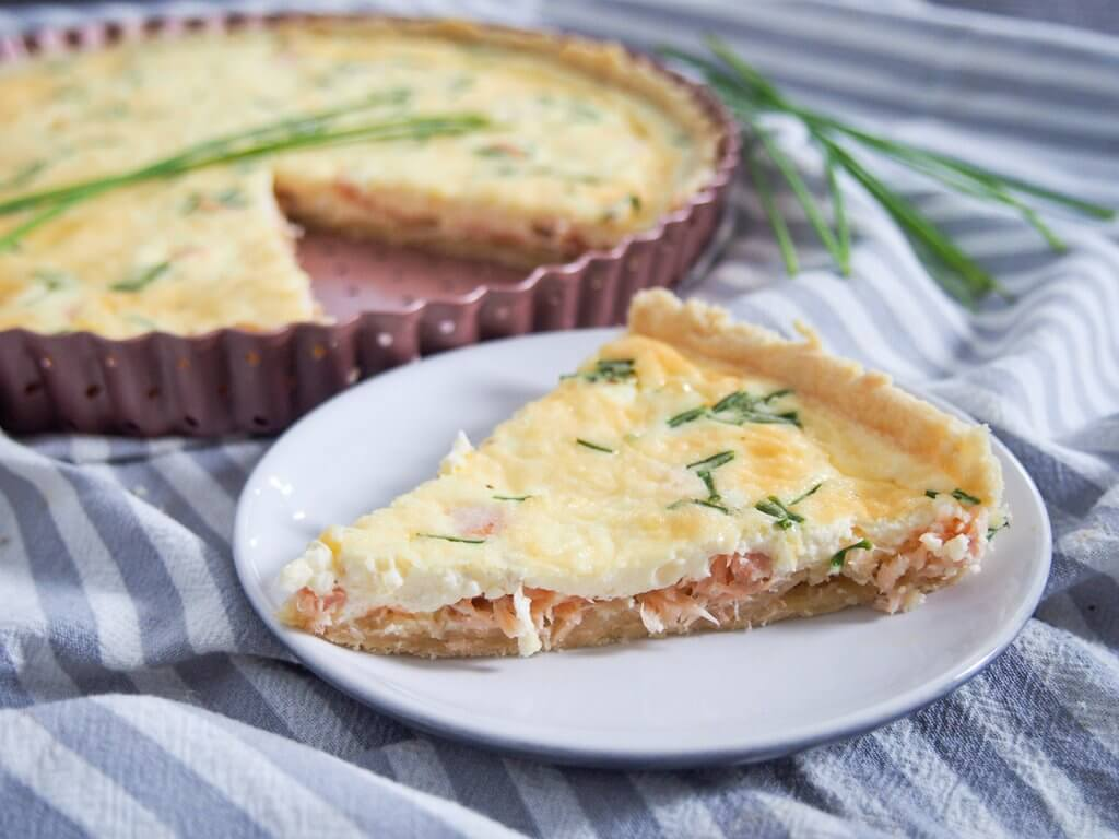 smoked salmon quiche with slice on plate in front