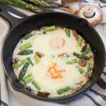 baked eggs with mushroom and asparagus in skillet