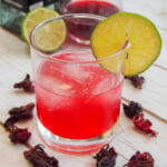 glass of hibiscus mezcal sour garnished with slice of lime