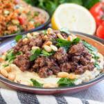 dish of hummus with lamb topped with parsley and pine nuts