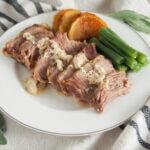 Milk-braised pork (maiale al latte) on plate with veg to side