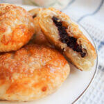 plate of eccles cakes with one split open showing filling