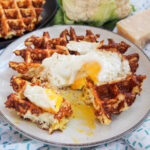 cauliflower waffle topped with egg with part cut and yolk on plate