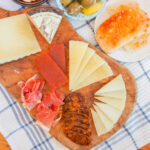 Spanish cheese plate viewed from overhead with slices of cheese, ham, membrillo and pan con tomate to side