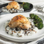 piece of baked tarragon chicken over rice with broccoli to side and second plate behind
