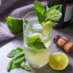 glass of champagne mojito garnished with mint and lime slice