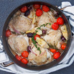 dish of chicken provencal with tomatoes and artichokes to top